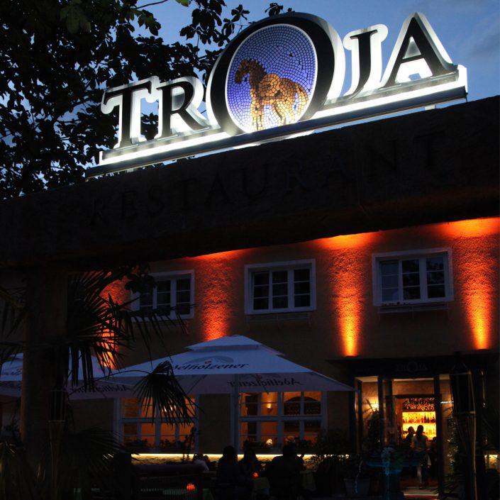 Restaurant Troja München - Troja Logo abends