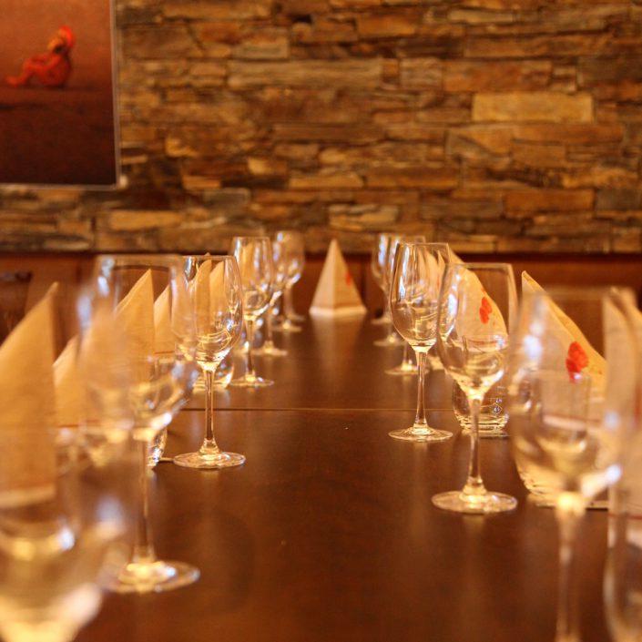 Restaurant Troja München - gedeckte Tafel, Gläser, Steinwand