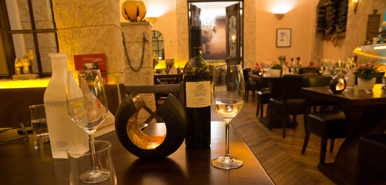 Home - Restaurant Troja München - Tisch mit Weißweingläsern, Leuchter und Wasserkaraffe